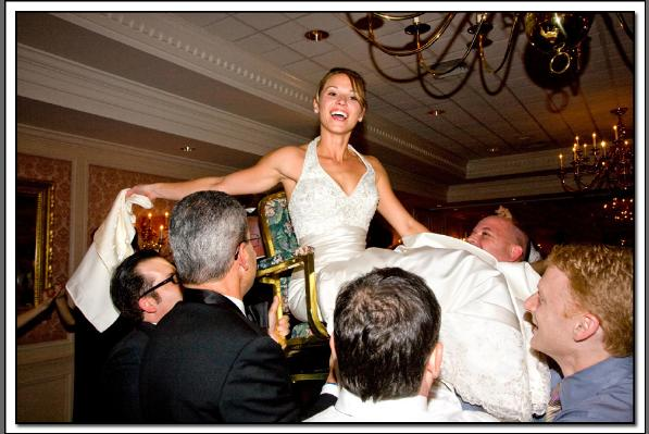 photo of bride being carried aloft in chair at wedding